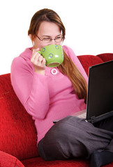 Young woman sitting on red couch with laptop