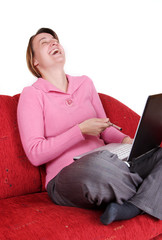 Young women laugh with laptop on red couch