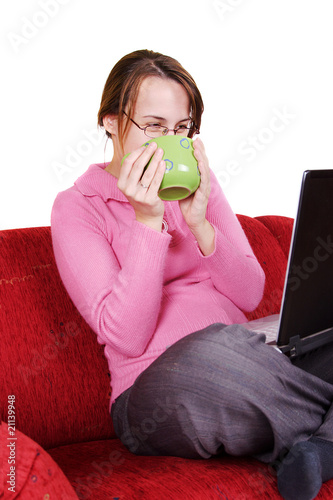 Young womand drinking from a green mug at home