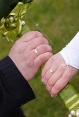 Couple with gold ring hold bunch of flower