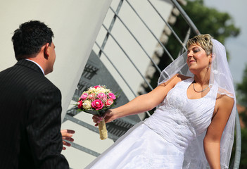 Bride hands over bouquet her groom