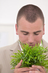 businessman holding and smelling a plant