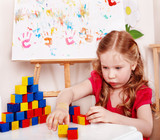 Child with wood block and construction set in play room.