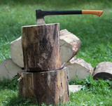 Chopping wood - ax in a log outdoors.