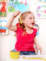 Child with picture and brush in play room.