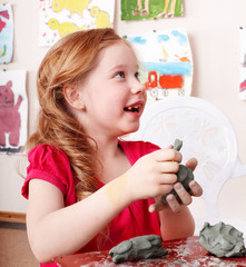 Child mould from clay in play room.