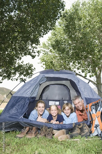 Family of four smiling from a tent