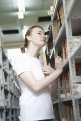 Young woman cranes neck at library shelving