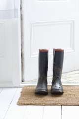 Muddy boots on door mat