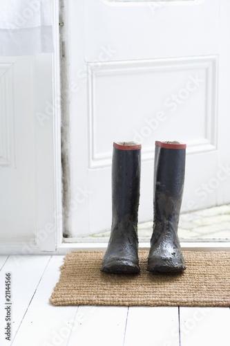 Muddy boots on door mat