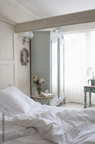 Unmade bed in sunlit beamed room