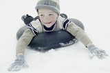 Boy in winter clothing sledging on an inner tyre