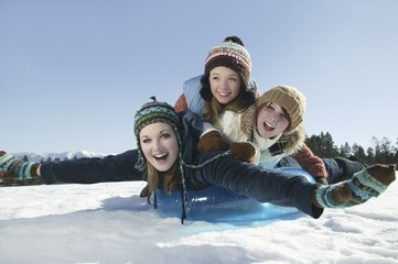 Three teenage girls lying on a sledge