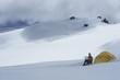 Hiker using laptop outside of tent on snowy mountain peak