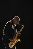 Man stands playing saxophone against black background