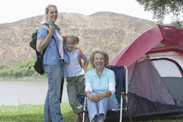 Mother, daughter and grand-daughter outside tent