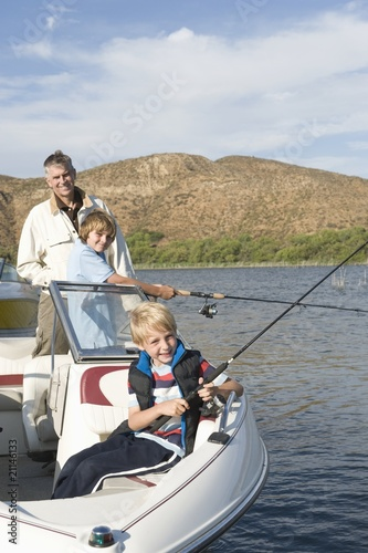 Father and sons fishing from a boat