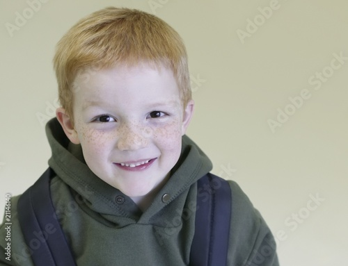 Schoolboy with redhair and freckles stands with backpack