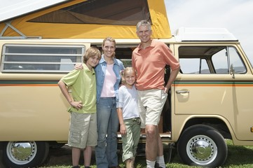 Family of four stand at campervan