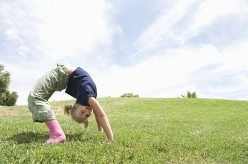 Bending over backwards, girl on grass