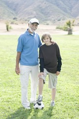 Portrait of grandfather and grand-son with football