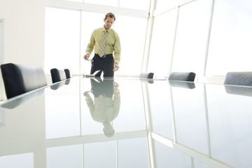 businessman stands at glass conference table