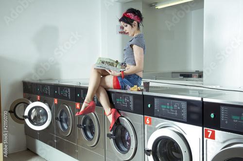 Junge Frau sitzt auf einer Waschmaschine