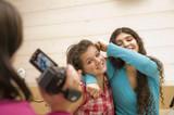 Jeunes filles chahutant et se filmant avec un caméscope poster