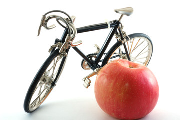 Toy bike standing next to red apple