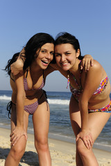 two happy girl friends on the beach