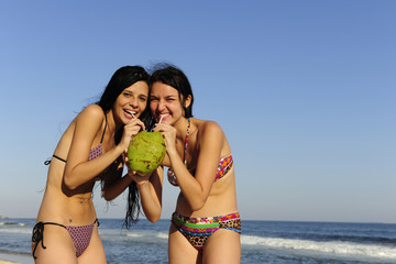 two young women drinking coconut water on the beach