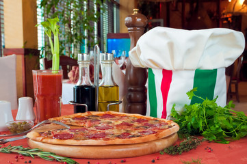 Closeup of a table with pizza and cook hat