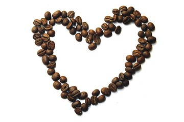 Heart made of coffee beans lying on the white background