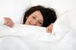 junge Frau liegt im Bett und lächelt