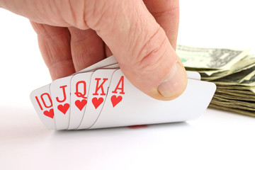 Man's hand holding a royal flush with cash