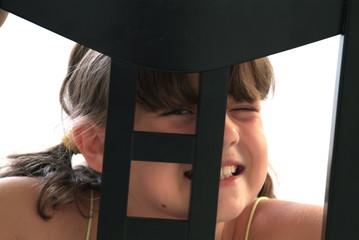 Ein Kind spielt und versteckt sich hinter dem Stuhl.Sample text.