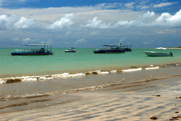 Boats in a crystalline green sea in Alagoas, Brazil