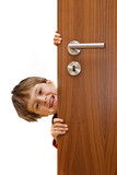 young little smiling boy looking over the door