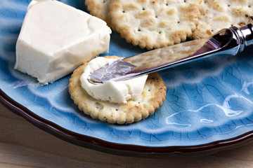 Delicious cheese and crackers with knife on blue plate