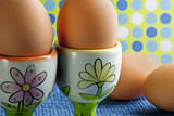 Beautiful floral egg cups holding two brown eggs