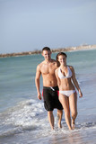 Beautiful woman and handsome man walking on  beach