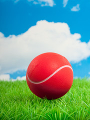 a red tennis ball on a green plastic lawn against a blue cloudy