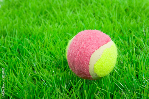 a pink yellow tennis ball on a green plastic lawn