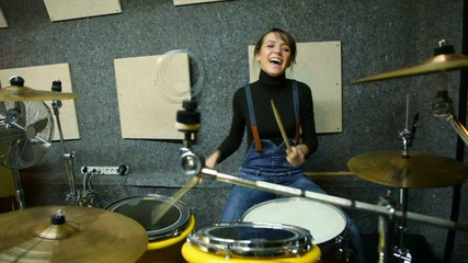 smiling girl playing on drums in studio