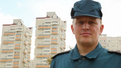 officer of rescue service standing against housing estate