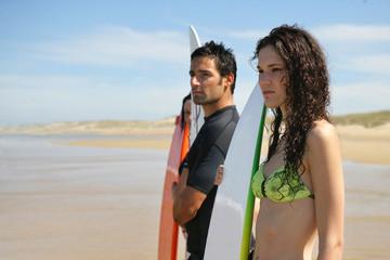 Amis avec planche de surf à la plage