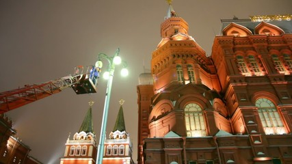 mounter changing workless street lamp on moscow night street