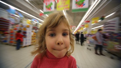 little girl sitting in moving shopping trolley in supermarket