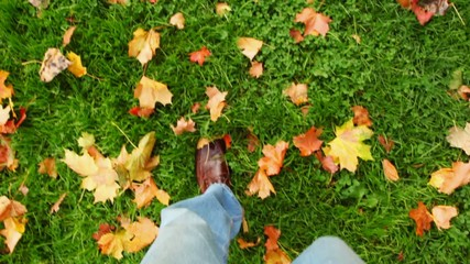 man walking on green grass with autumn leaves, view to foots