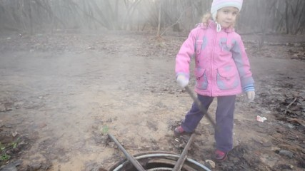 little girl with stick standing near steaming sewer manhole